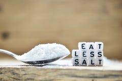 Nahaufnahme von Eat weniger Salztext geschrieben mit Plastikbuchstaben nahe einem Salzlöffel lizenzfreie stockfotos