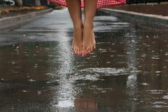 Nahaufnahme von ein Mädchen ` s Füßen, die in eine Pfütze nach einem Sommerregen tanzen lizenzfreie stockfotos