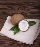 Nahaufnahme von einem exotischen ganzen und ein gebrochen in den halben Kokosnüssen mit grünen Blättern auf einem grauen Gewebe u stockbild