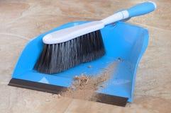 Nahaufnahme von einem kleinen wischen Besen mit kurzem Griff und eine Müllschippe mit wirklicher Schmutz abgefegtem Boden Stockbilder
