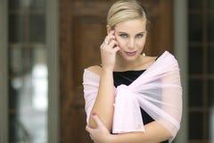 Nahaufnahme von einem schönen blonden mit einem schwarzen Samtkleid und einer rosa Verpackung Lizenzfreie Stockbilder