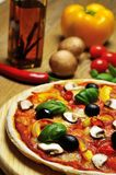 Nahaufnahme von einer Pizza, von einem Öl und von Bestandteilen Stockfotografie