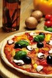 Nahaufnahme von einer vegetarischen Pizza, von einem Öl und von Bestandteilen Stockbilder