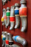 Nahaufnahme von Farbenrohren in Form der Finger auf der roten Wand, ungewöhnliche Farben ÖlFarbfernsehen, gelb, rot, blau, grün stockbild