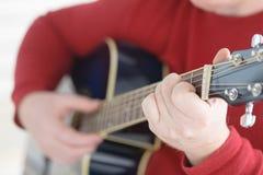 Nahaufnahme von Fingern vom Spielen der Akustikgitarre Lizenzfreies Stockfoto