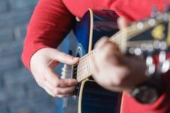 Nahaufnahme von Fingern vom Spielen der Akustikgitarre Lizenzfreie Stockfotografie