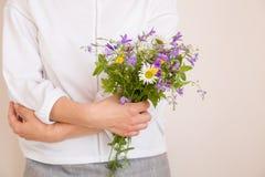 Nahaufnahme von Frau ` s übergibt das Halten des schönen Bündels wilder Blumen Mädchen mit Sommerblumenstrauß an der weißen Wand lizenzfreies stockfoto