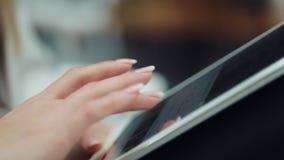 Nahaufnahme von Frau ` s Finger, der mit einer Tablette auf ihren Knien arbeitet stock video