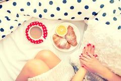 Nahaufnahme von Frauenbeinen und -frühstück im Bett mit Hörnchen, Kaffee und Orangensaft Stockbilder