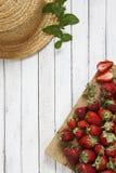 Nahaufnahme von frischen roten Erdbeeren auf hölzernem Brett auf weißem Hintergrund der Weinlese mit Sommerhut Stockbilder