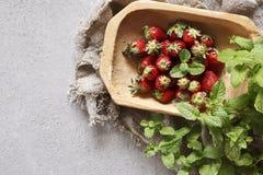Nahaufnahme von frischen roten Erdbeeren auf hölzerner Platte mit grünen tadellosen Blättern auf konkretem Hintergrund Lizenzfreie Stockfotografie