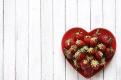 Nahaufnahme von frischen roten Erdbeeren auf roter Herz-förmiger Platte auf Weinleseweißhintergrund Stockbild
