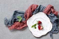 Nahaufnahme von frischen roten Erdbeeren auf weißer Platte auf konkretem Hintergrund mit farbigem Schal Stockfoto
