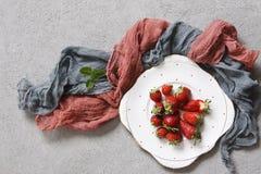 Nahaufnahme von frischen roten Erdbeeren auf weißer Platte auf konkretem Hintergrund mit farbigem Schal Lizenzfreie Stockfotografie