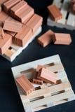 Nahaufnahme von gefallenen Ziegelsteinen auf hölzerner Palette Stockfotos