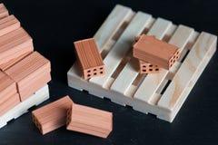 Nahaufnahme von gefallenen Ziegelsteinen auf hölzerner Palette Stockfoto