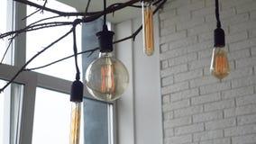 Nahaufnahme von gelben Lampen der Weinlese von verschiedenen Formen in einem hellen Raum gegen eine Backsteinmauer und ein Fenste stock video