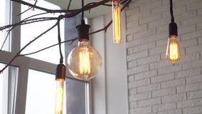 Nahaufnahme von gelben Lampen der Weinlese von verschiedenen Formen in einem hellen Raum gegen eine Backsteinmauer und ein Fenste stock footage