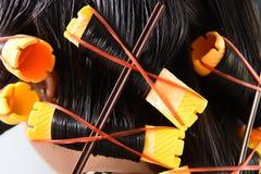 Nahaufnahme von gelben Lockenwicklern im Haar Stockbild