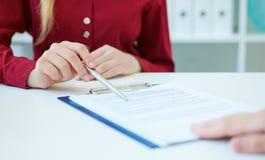 Nahaufnahme von Geschäftsfrau ` s übergibt das Zeigen ihrem neuen Teilhaber der Vertragsbedingungen oder des Vertrages Gerade Hän stockfoto