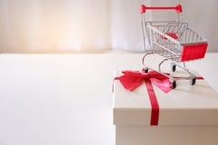 Nahaufnahme von Geschenkboxen und von Einkaufswagen auf weißem Schreibtisch stockbilder