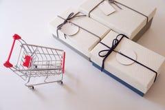 Nahaufnahme von Geschenkboxen und von Einkaufswagen auf weißem Schreibtisch lizenzfreie stockfotos
