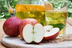 Nahaufnahme von geschnittenem Apple mit Glas und Pitcher Saft Stockfotos