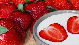 Nahaufnahme von geschnittenen und ganzen Erdbeeren mit selbst gemachtem Jogurt Lizenzfreie Stockbilder