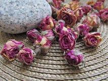 Nahaufnahme von getrockneten tearoses auf Weidenwolldeckenhintergrund lizenzfreie stockfotos