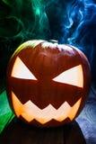 Nahaufnahme von glühenden Kürbisen für Halloween auf hölzernem Schreibtisch Lizenzfreie Stockfotos