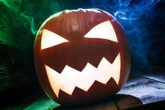 Nahaufnahme von glühenden Kürbisen für Halloween mit blauem und grünem Rauche Stockbild