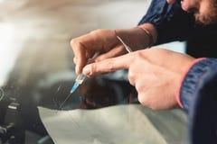 Nahaufnahme von Hände des Berufswindschutzscheibenschlossers füllt einen Sprung im Glas mit einem speziellen Polymer durch a lizenzfreie stockbilder