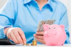 Nahaufnahme von Händen der Geschäftsfrau, der Münzen und des Sparschweins stockbilder