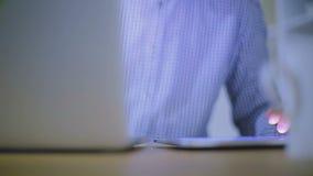 Nahaufnahme von Händen des Kerls, der im Büro hinter dem Laptop arbeitet stock video