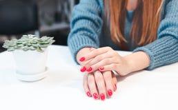 Nahaufnahme von Händen einer jungen Frau mit roter Maniküre lizenzfreies stockfoto