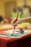 Nahaufnahme von Händen mit Kunstbürste Gebrauch als Musterfülle, Hintergrund Stockfotos