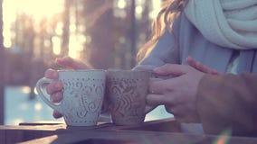Nahaufnahme von Händen des Mannes und der Frau, die draußen heißen Tee in den Bechern im Winter halten stock footage