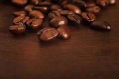 Nahaufnahme von Kaffeebohnen auf einer dunklen Holzoberfläche Lizenzfreie Stockfotos