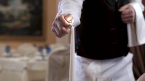 Nahaufnahme von Kellnern übergeben das ` s, das Kerzen im eleganten Restaurant beleuchtet Fokus ist auf einer Kerze Romantisches  stock video footage