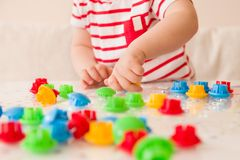 Nahaufnahme von Kind-` s Hand, die helles Mosaik nimmt, zerteilt Farben zu Hause spielen und lernend Stockfotografie