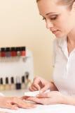 Nahaufnahme von Kosmetikerhandarchivierungsnägeln der Frau im Salon Stockfotos