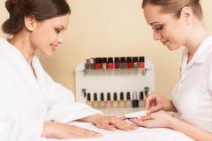 Nahaufnahme von Kosmetikerhandarchivierungsnägeln der Frau im Salon Lizenzfreie Stockfotos