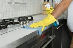 Nahaufnahme von männlichen Händen in den Gummihandschuhen, die den Kocher säubern Lizenzfreies Stockbild