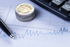 Nahaufnahme von Münzen und von Diagramm Stockbilder