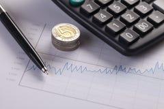 Nahaufnahme von Münzen und von Diagramm Stockfotos