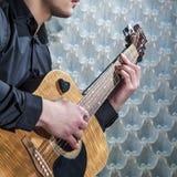 Nahaufnahme von man& x27; s-Hände, die auf Akustikgitarre spielen Stockfotografie