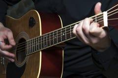 Nahaufnahme von man& x27; s-Hände, die auf Gitarre spielen Lizenzfreie Stockfotografie