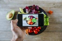 Nahaufnahme von Mann ` s Hand, die ein Foto zu einem Salat macht Stockfotos