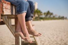 Nahaufnahme von Mann ` s und Frau ` s von Füßen Leute, die auf der hölzernen Plattform auf dem Strand sitzen Lizenzfreie Stockfotos