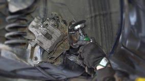 Nahaufnahme von Mechanikerarbeitskrafthänden reiben rostige Autobremsanlageteile mit Schleifer stock footage